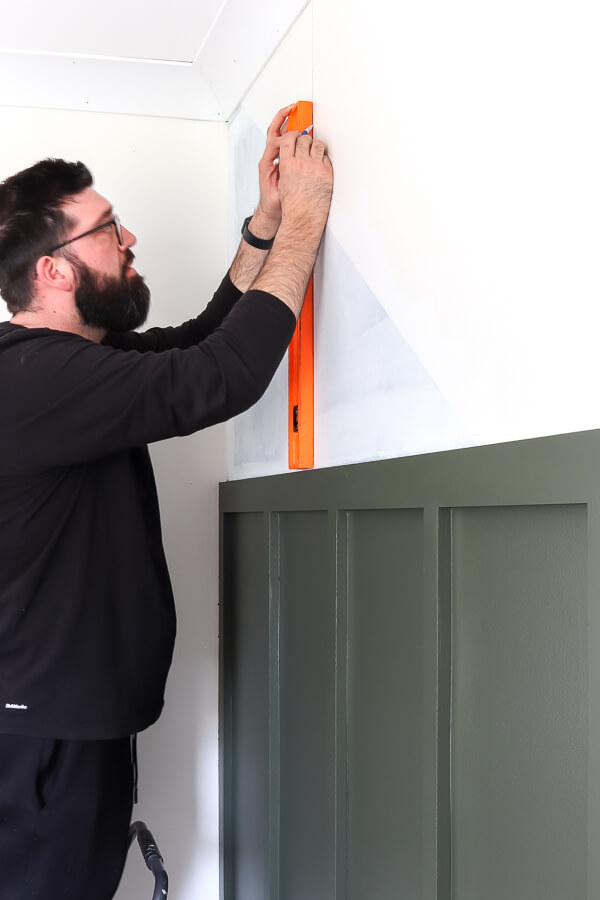 man with orange level measuring for removable wallpaper