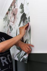 womans hand installing Rocky Mountain Decals Queen ann removable wallpaper