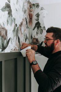 man with straight edge cutting Rocky Mountain Queen Ann floral wallpaper