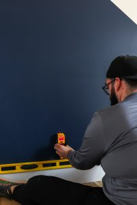 Man with hat with yellow level using a studfinder