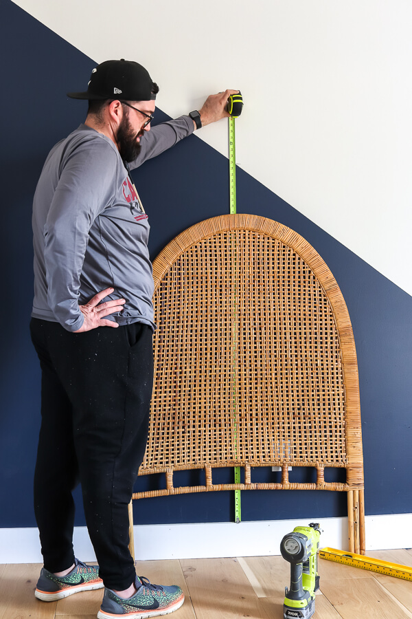 man in hat and gray long sleeve shirt measuring vintage rattan headboard up against navy and white accent wall