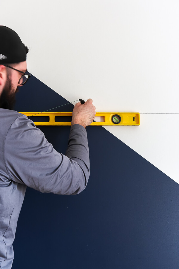 man in hat with yellow level marking wall in pencil