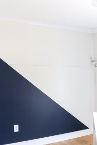accent wall in Sherwin Williams Alabaster and Naval with pencil line to measure for board and batten