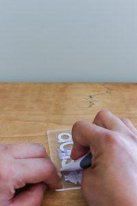 woman's hand adding white vinyl to acrylic tag