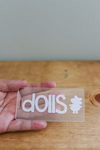 acrylic tag with white vinyl dolls on it against a wood background