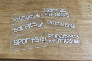 acrylic tags for toy organization on wood background