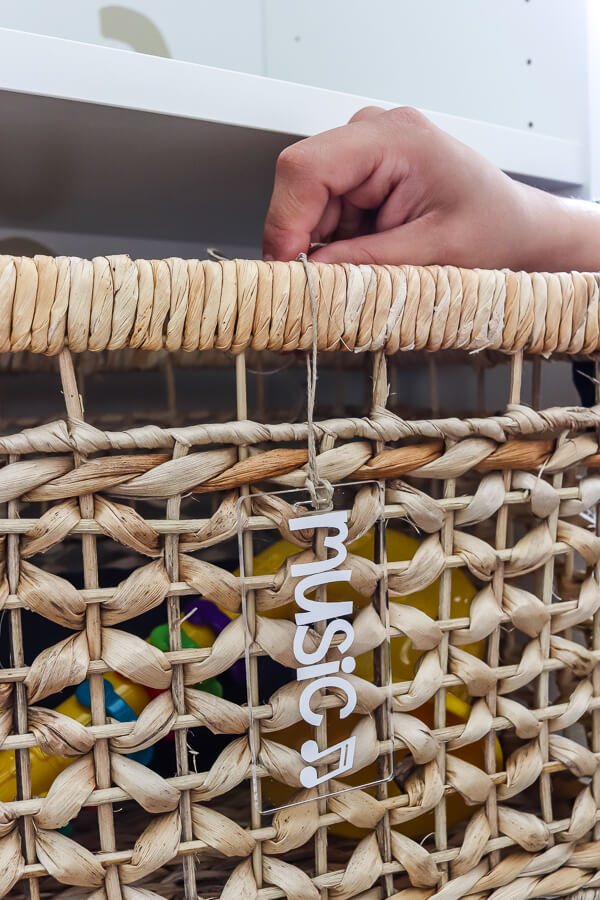 rattan basket with acrylic tag that says music toy storage organization