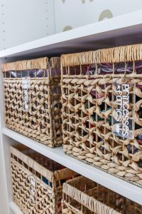 4 rattan baskets for toy storage and organization on white Ikea Billy bookshelves