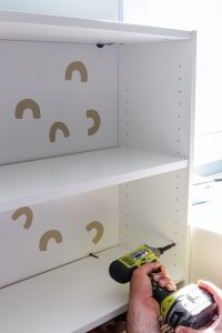 hand with Ryobi impact driver screwing into Billy bookcases