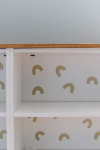 white Ikea Billy bookcase with tan U shaped decals and a wood top