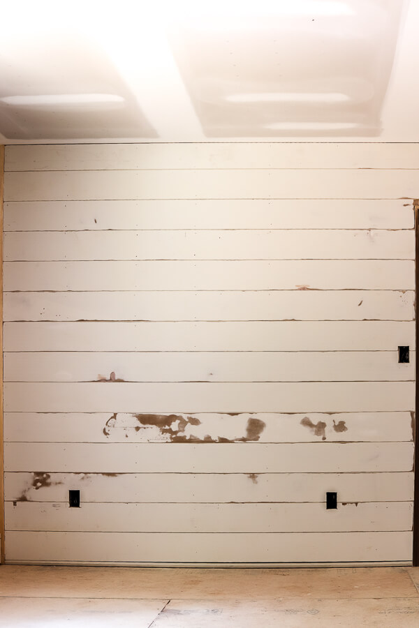 white shiplap feature wall in primary bedroom