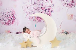 baby girl newborn photo wearing a crown sleeping on a crescent moon from Charmarie Photography newborn photos