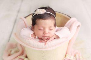 baby girl newborn photos wearing pink in a bucket sleeping from Charmarie Photography newborn photos