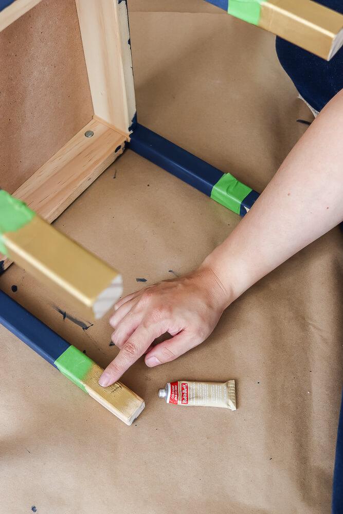 woman applying Rub n Buff with finger to Ikea Latt table chair leg
