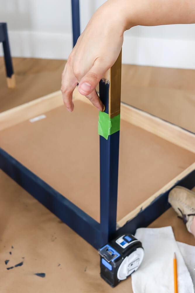 woman applying Rub n Buff with finger to Ikea Latt table leg