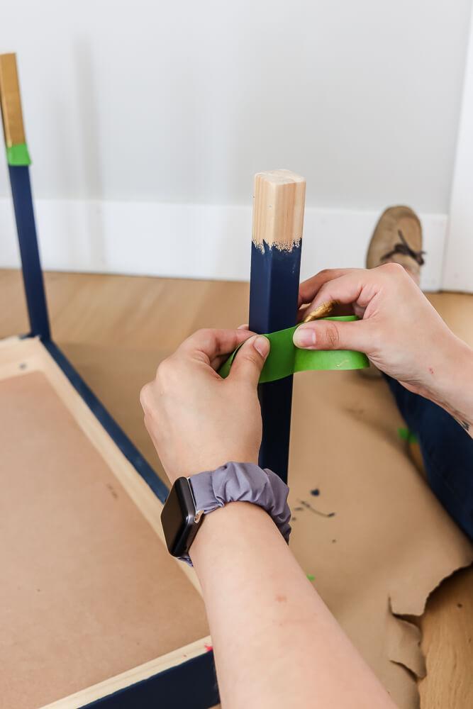 woman's hand marking off Ikea Latt table leg with green Frog painter's tape