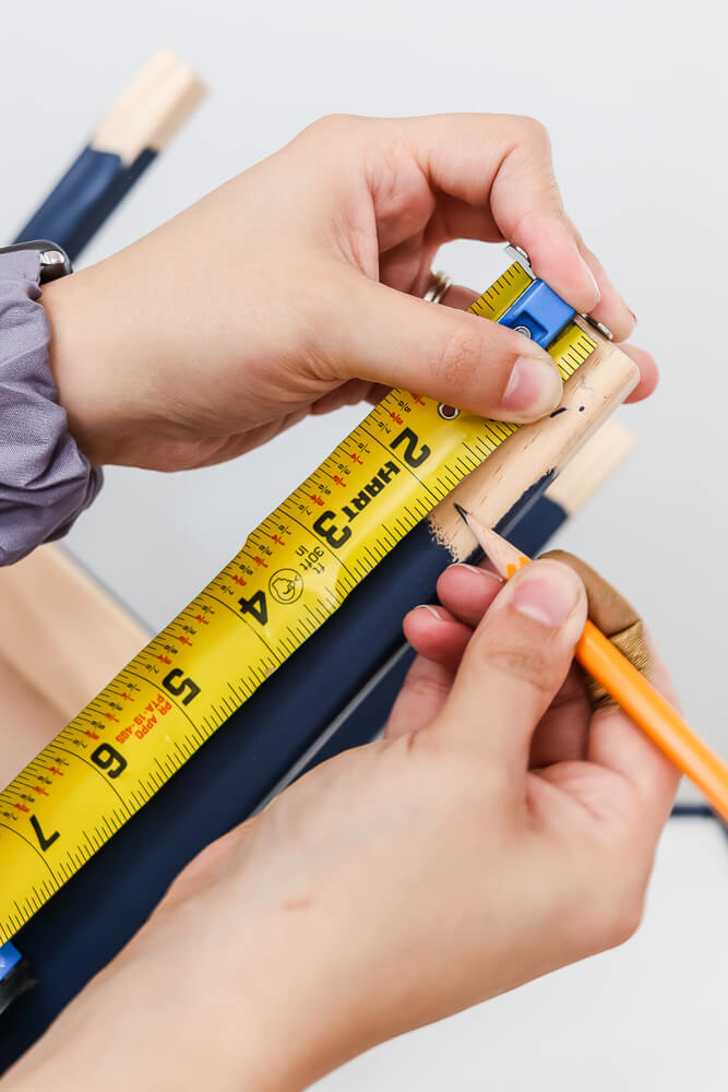 woman using tape measure to measure Ikea Latt table leg