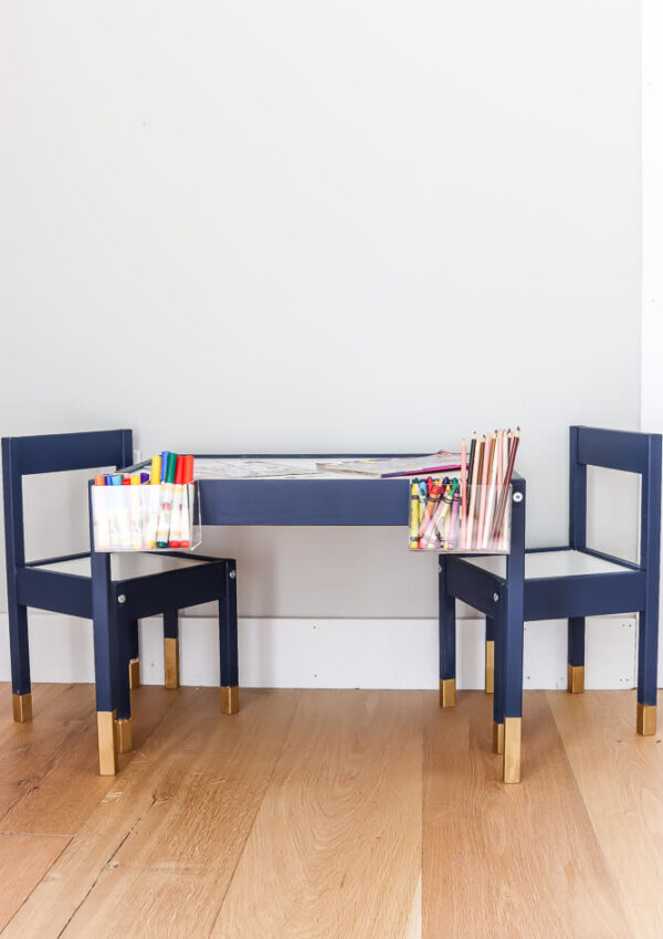Ikea Latt table hack painted navy with Gold Rub n Buff legs and clear acrylic containers holding pencils, crayons, and markers