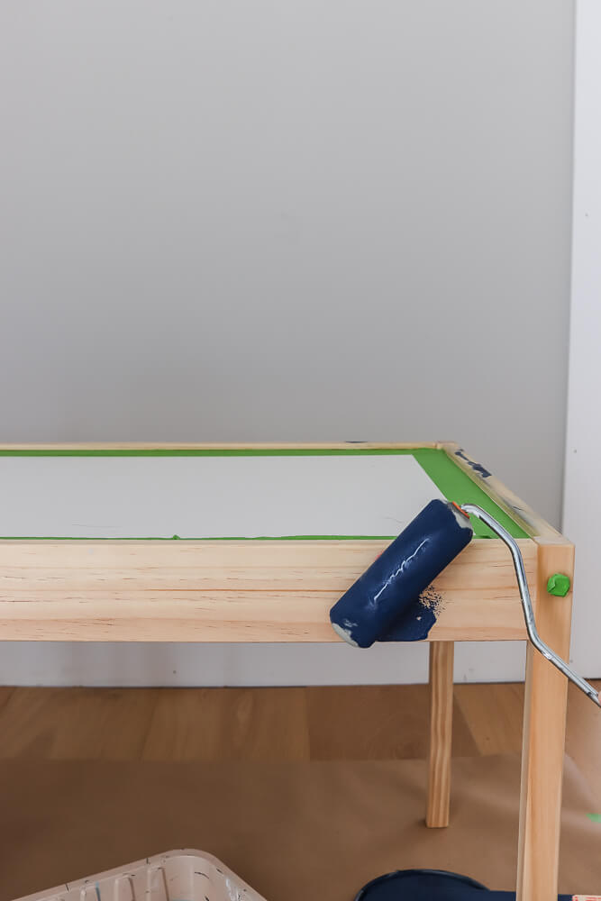 Ikea Latt table with green Frog tape with paint roller with Sherwin Williams Naval paint