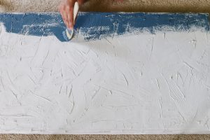 woman's hand painting navy on textured canvas abstract art