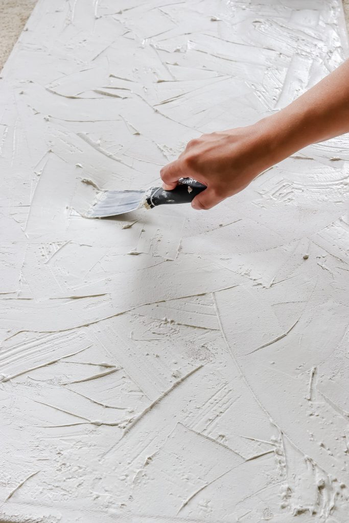 woman using putty knife to spread joint compound on canvas