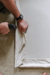 man's hands stapling canvas over wood frame