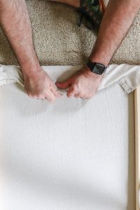 man's hands stretching canvas over wood frame