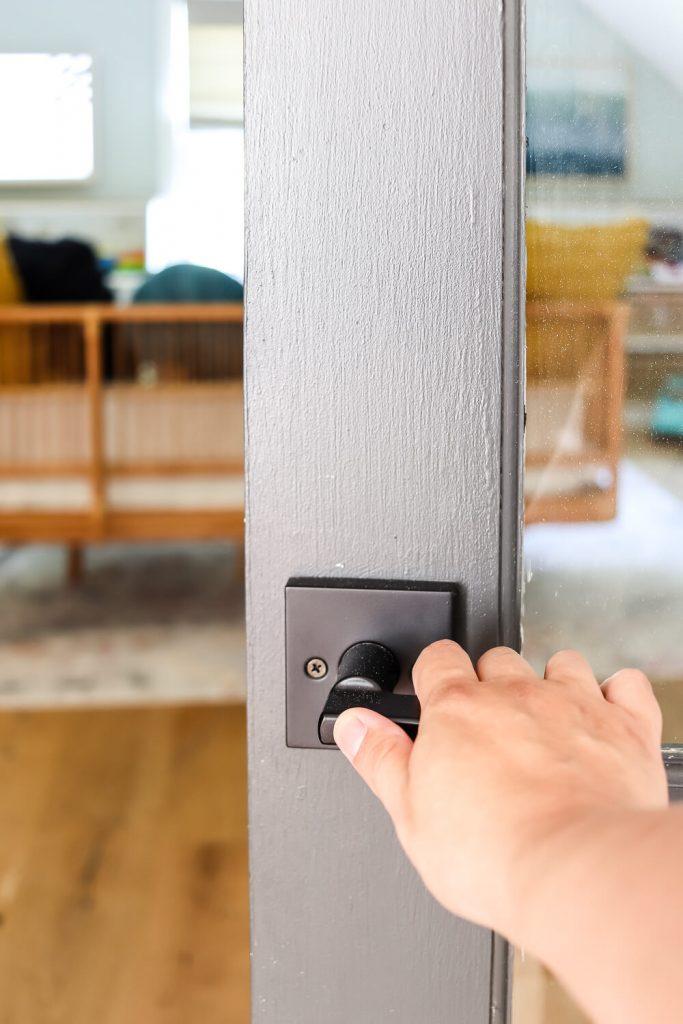 woman's hand on black doorknob