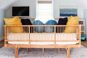 World Market rattan daybed with navy, yellow and turquoise pillows