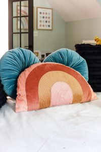 rainbow pillow in front of 2 turquoise round pillows