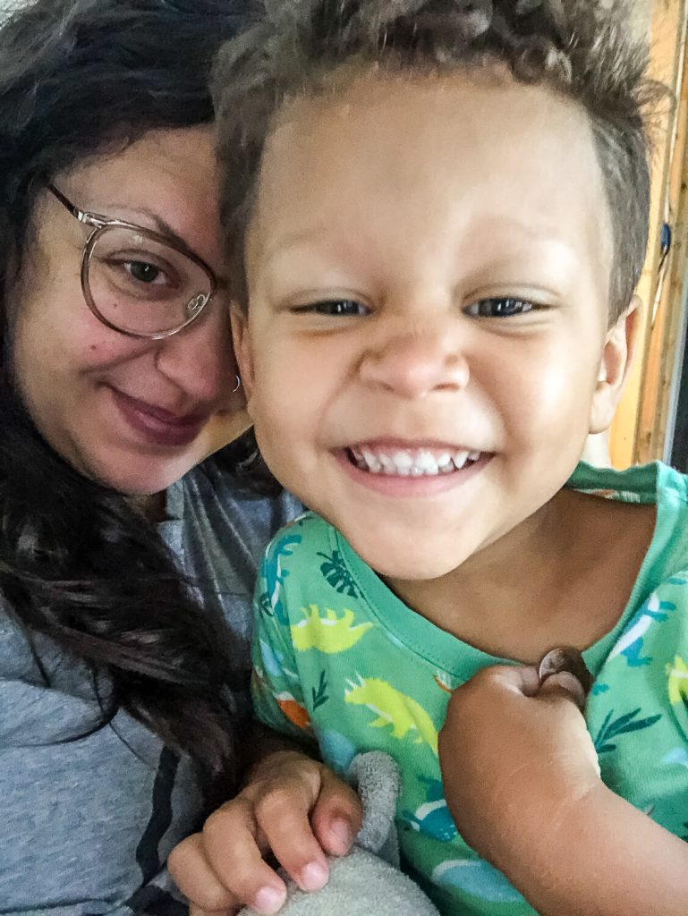 woman with dark hair and glasses with smiling toddler boy
