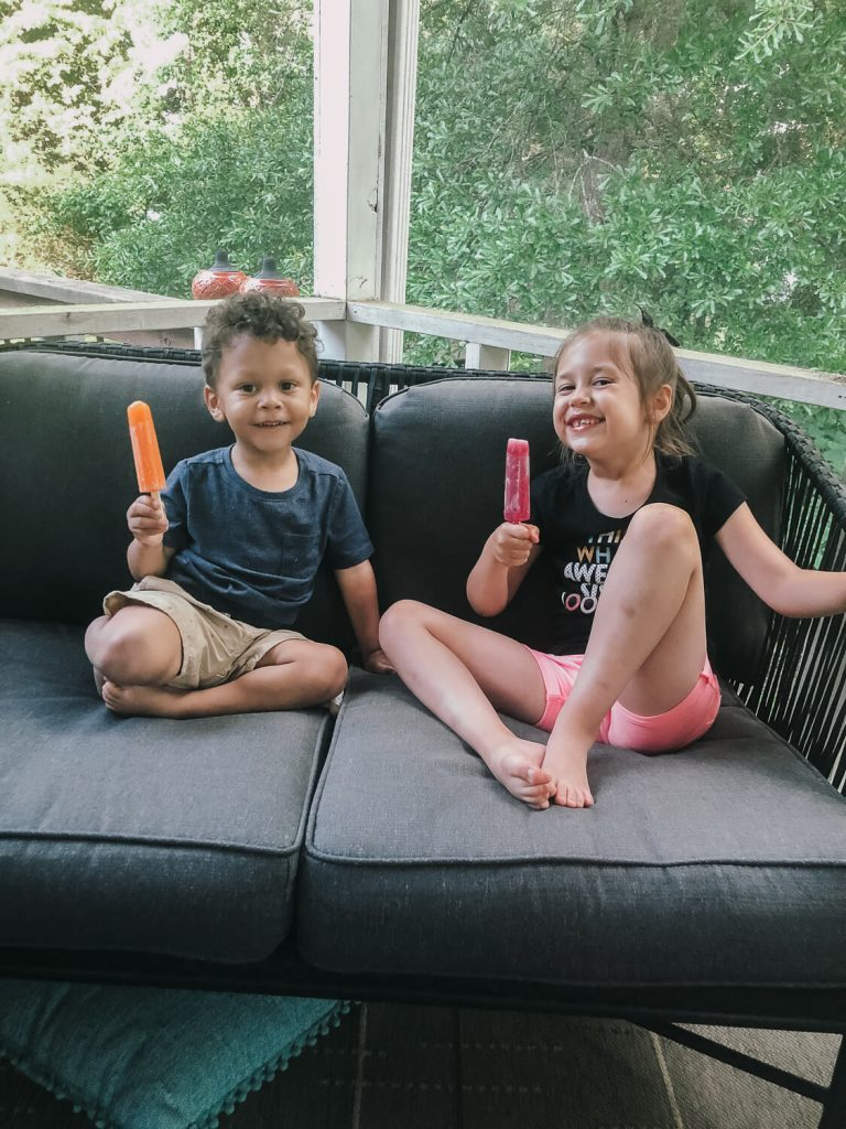 kids sitting on grey outdoor couch eating popsicles