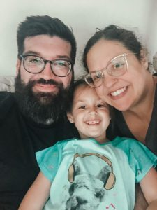 man and woman with glasses with young girl