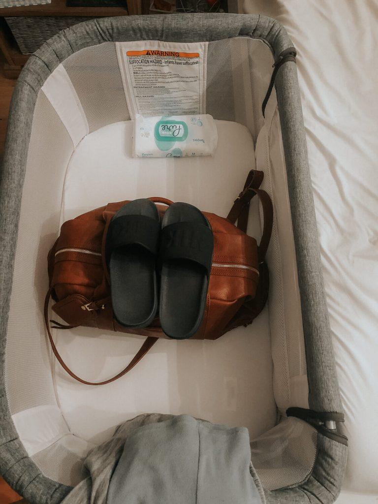 bedside bassinet with leather bag and black nike slides