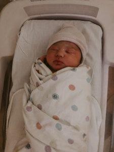 newborn baby girl swaddled in hospital