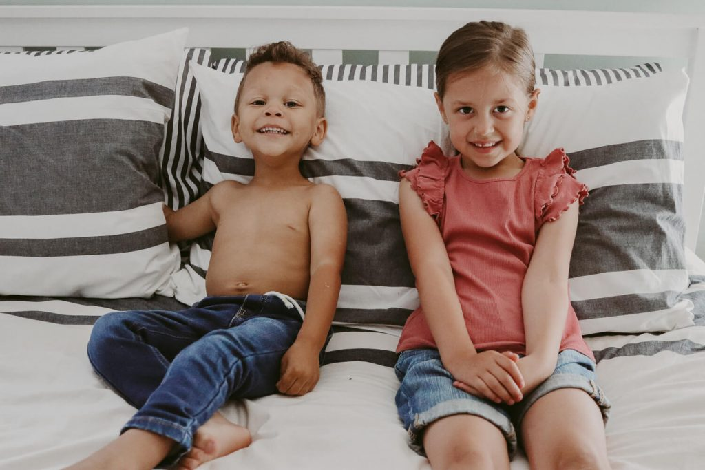 young girl and toddler boy on bed with white and gray bedding