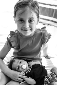 young girl holding baby sister