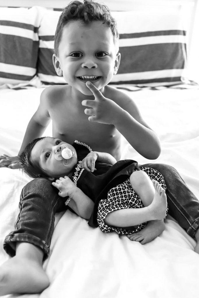 toddler boy holding baby sister