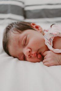 newborn baby girl laying on bed sleeping