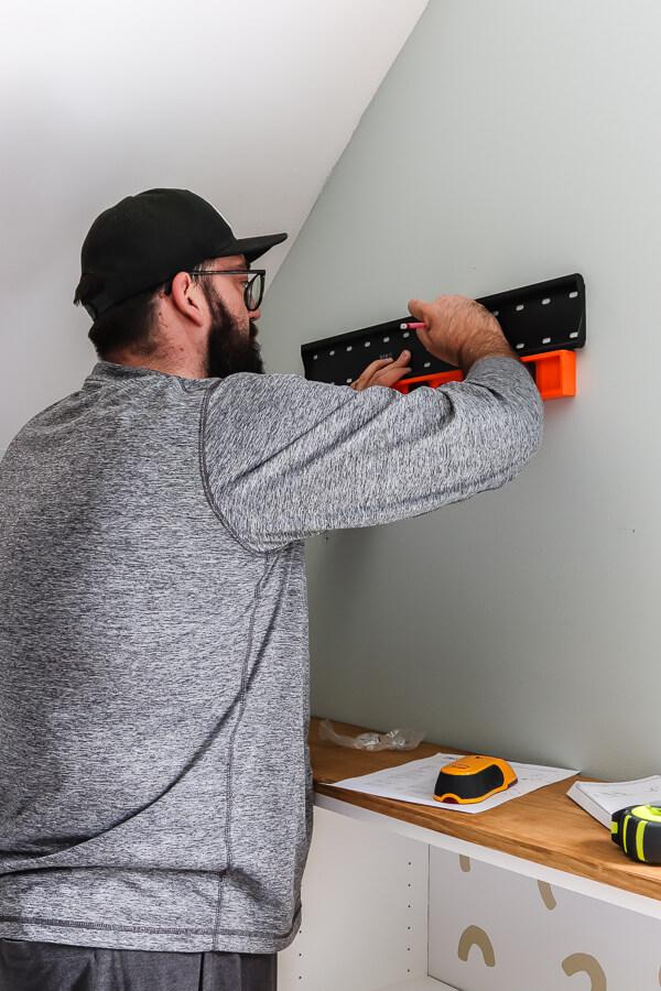 man using orange level marking where TV mount should be