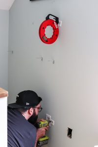 man in black hat with drill pulling wires through the wall to hide cords