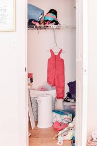 girls pink ski bib hanging in messy closet