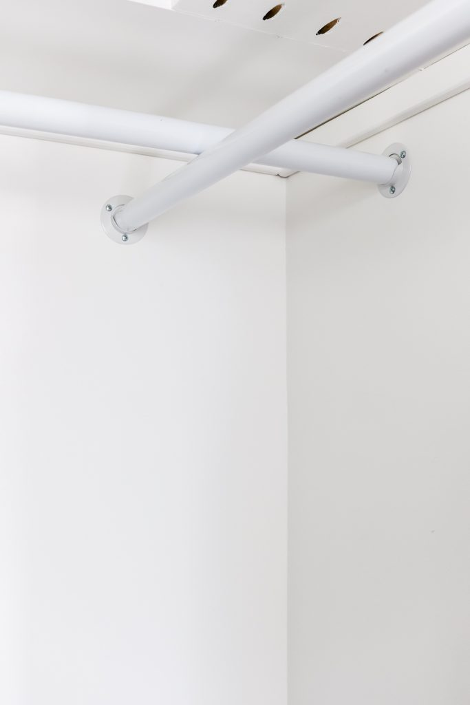 white closet rods in a corner of a closet with white walls