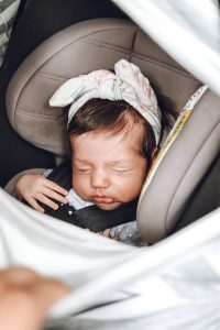 little girl with headband in a carseat