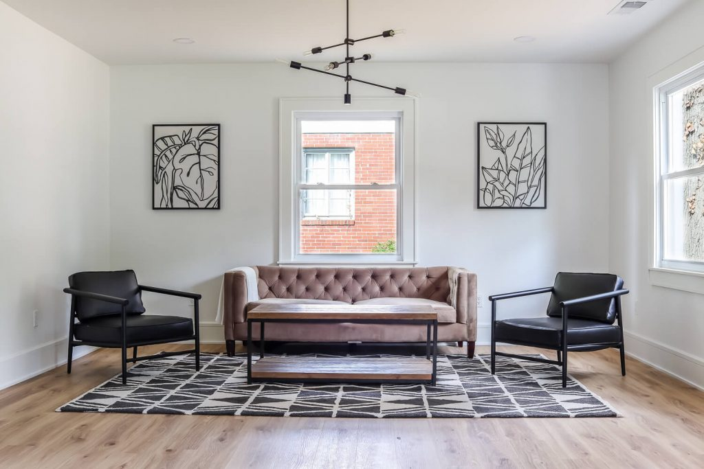 white walls in living room with black side chairs and black sputnik light fixture
