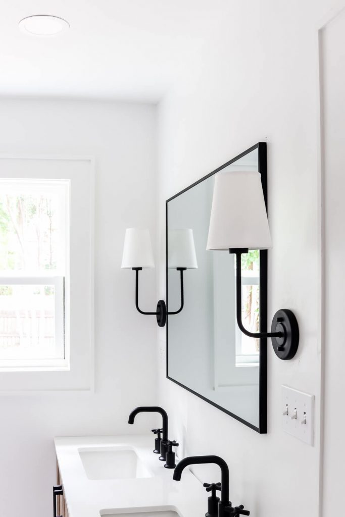 black sconce with white cover and black frame mirror in bathroom