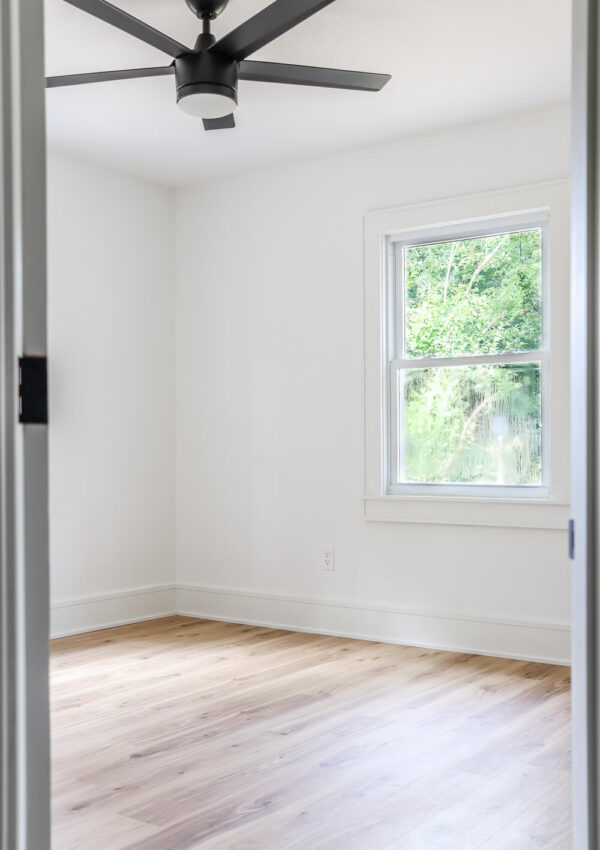 guest room with white wood floors and Sherwin Williams Pure White walls