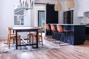 kitchen with black island and leather barstools with rattan pendants