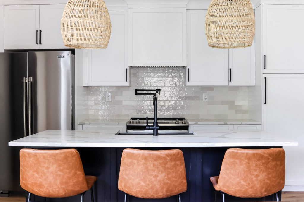 white upper cabinets and black kitchen island with leather barstools and rattan pendants