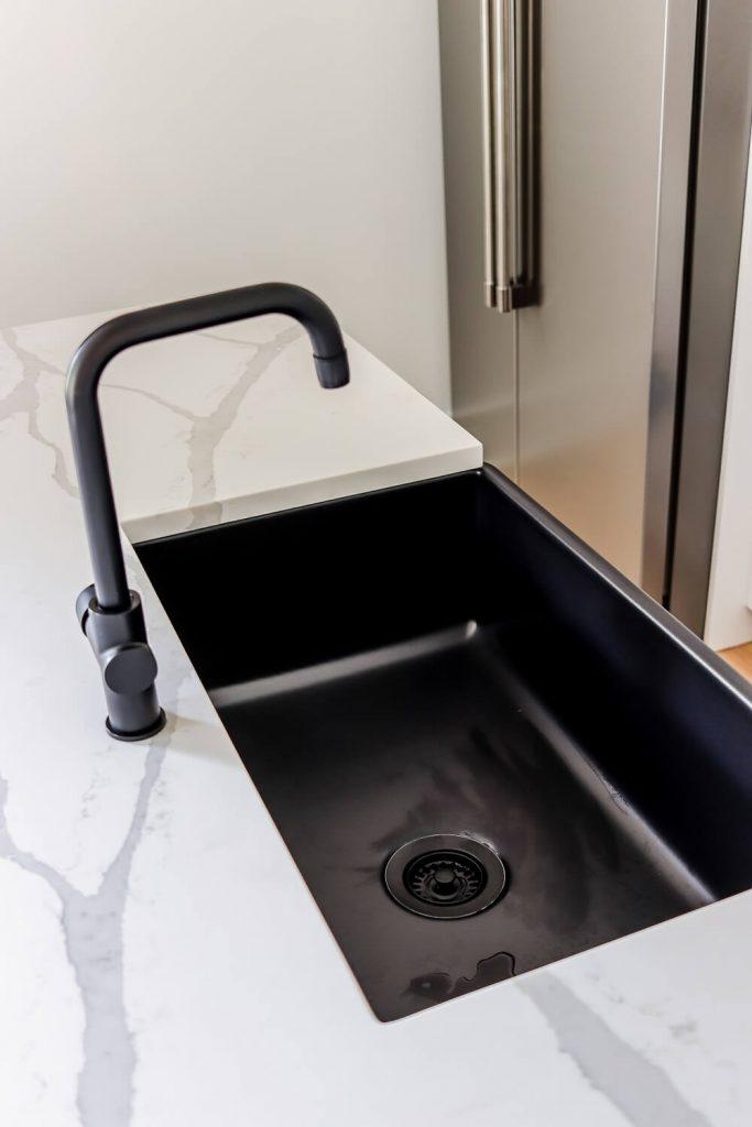 white quartz countertops, matte black faucet and matte black farmhouse sink from Sinkology